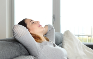 Happy relaxed woman resting on a couch in her comfortable and healthy home