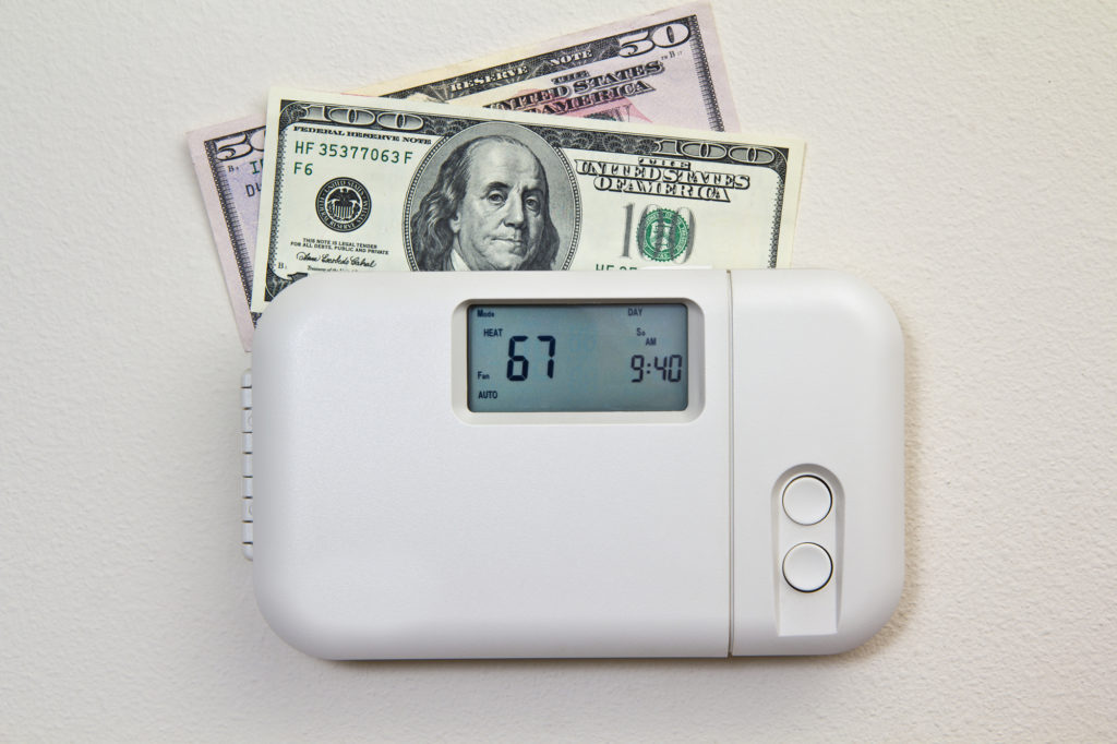 In door heating thermostat set at a room temperature and money