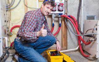 Happy handyman showing thumbs up while working on a furnace.