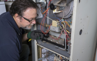 HVAC technician that is checking on a humming furnace