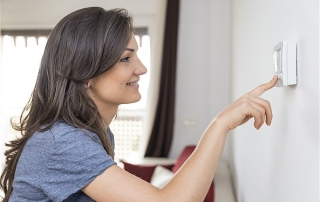 woman using thermostat to adjust a/c unit